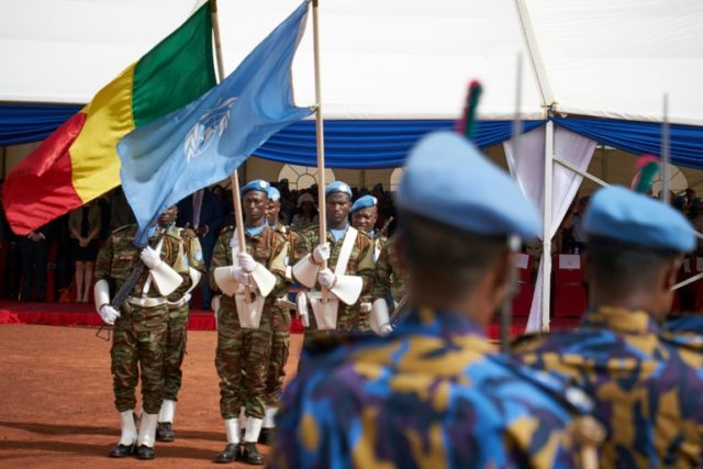 Soldiers hold the UN and Malian flags during a Peacekeepers' Day ceremony at the operating base of MINUSMA, the UN's mission in Mali, on May 28, 2018