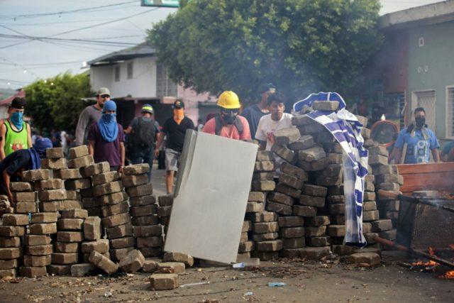 Demonstrators protect themselves from tear gas and bullets in the flashpoint Nicaraguan town of Masaya -- violence in the country since April has left at least 134 people dead