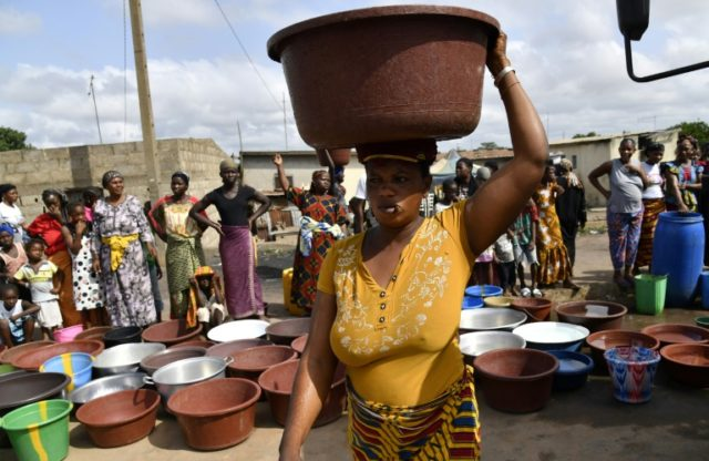 An Ivorian woman carries a heavy load after a distribution of safe drinking water in Bouake in early June