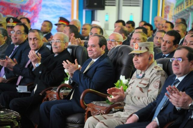 A handout picture released by the Egyptian Presidency on January 31, 2018 shows President Abdel Fattah al-Sisi(C)attending an ceremony for the launch of an offshore gas field accompanied by Housing Minister Mostafa Madbouli (L) and other officials