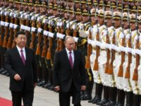Russia's President Vladimir Putin reviews a military honour guard with Chinese counterpart Xi Jinping during a welcoming ceremony outside the Great Hall of the People in Beijing