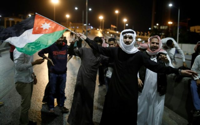 Protestors wave Jordanian flags during a protest near the prime minister's office in Amman, Jordan, on June 6, 2018