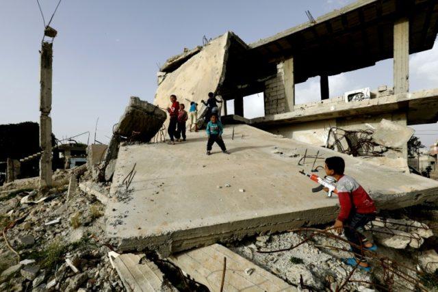 Syrian children play among destroyed buildings in Kobane