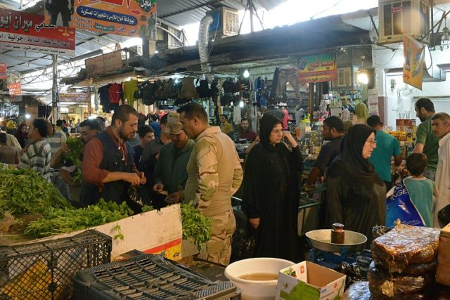 Iraqi men and women buy food in an open air market in Mosul after breaking the fast during Ramadan on May 24, 2018, as the holy month has one on without major violence unlike previous years when it was rocked by deadly attacks