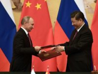 Putin (L) and Chinese President Xi Jinping (R) exchange documents during a signing ceremony inside the Great Hall of the People in Beijing on June 8