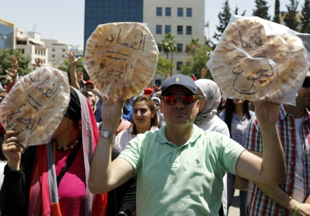 "Jordanian protesters hold loaves of bread inscribed in Arabic with the words ""corruption=hunger"" during an anti-austerity rally on June 6, 2018 outside the Amman headquarters of the federation of trade unions"