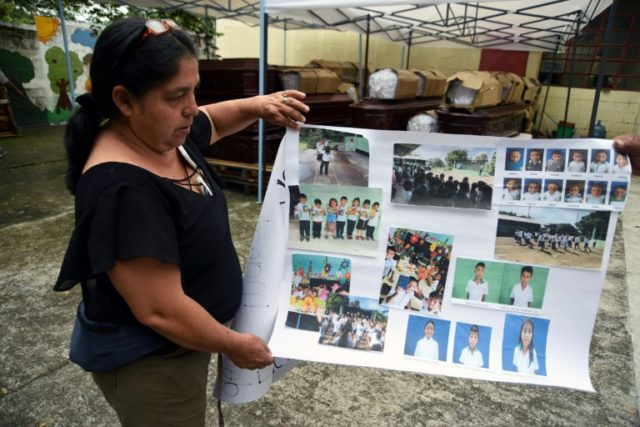 School teacher Milvia Lopez, standing in an improvised morgue in the Guatemalan town of Escuintla, shows pictures of some of her students who died or remain missing after the eruption of the Fuego volcano