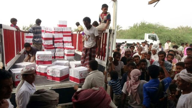 Yemenis drop off boxes of humanitarian aid provided by the Emirati Red Crescent in the coastal town of Mujailis, south of the city of Hodeida, on June 6, 2018