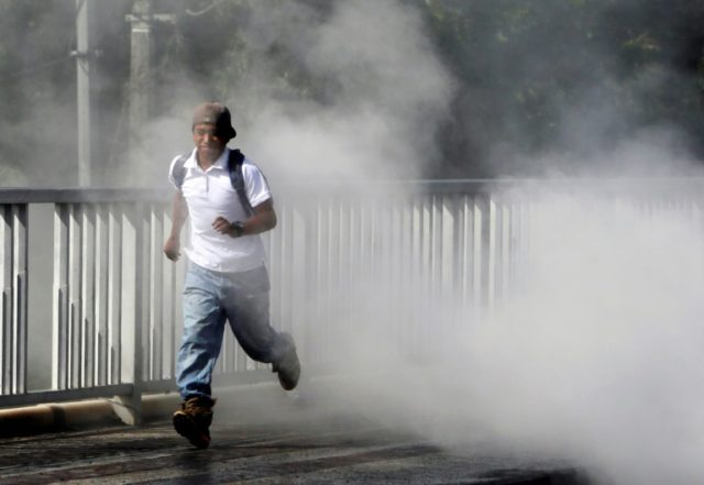 A man runs from the smoke of burning tires, in the city of Sebaco, Nicaragua
