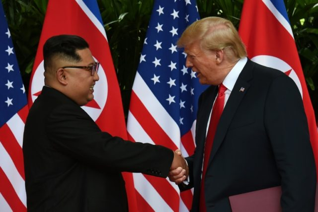North Korea's leader Kim Jong Un (L) shakes hands with US President Donald Trump (R) after taking part in a signing ceremony at the end of their historic US-North Korea summit
