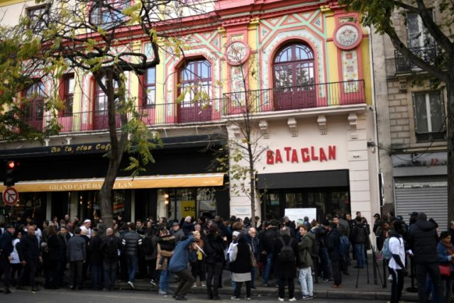 People stand in front of the Bataclan concert venue during ceremonies across Paris marking the second anniversary of the terror attacks of November 2015