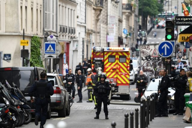 Police officers stand near the site of an ongoing hostage situation in central Paris