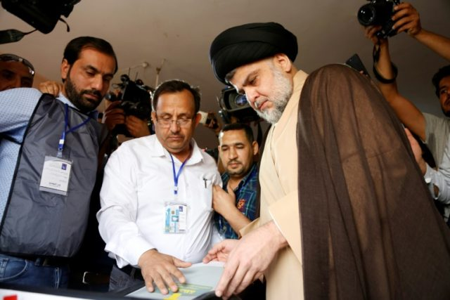 "Iraqi Shiite cleric and leader Moqtada al-Sadr (C-R), seen here voting in Najaf on May 12, said he had formed a ""true alliance"" with Hadi al-Ameri"