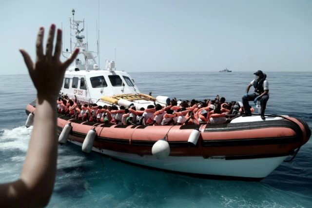 This handout picture from French NGO Doctors Without Borders(MSF)/SOS Mediterranee shows rescued migrants and MSF personnel onboard an Italian coastguard ship following their transfer from the ship Aquarius.