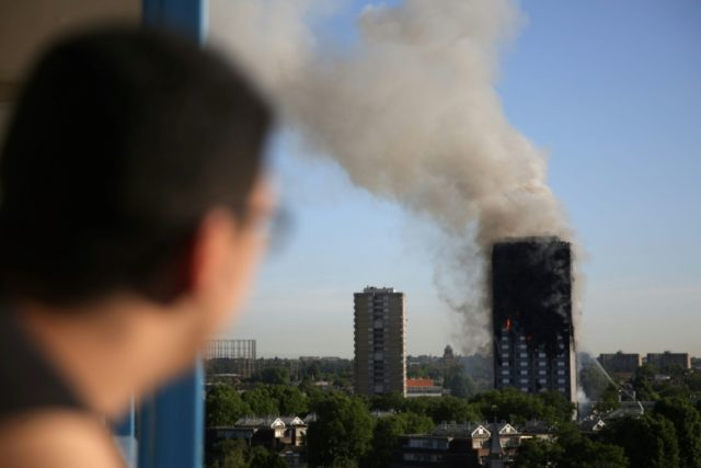 A resident of a nearby council estate watches smoke billowing from Grenfell Tower in west London, in a file photo taken on June 14, 2017