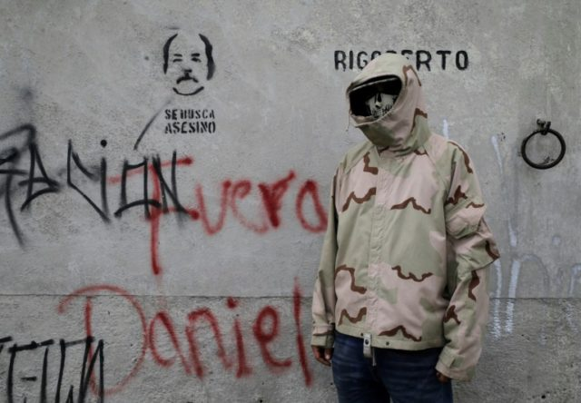 "A student poses next to graffiti that reads ""Daniel get out!"" in allusion to the embattled President Daniel Ortega"