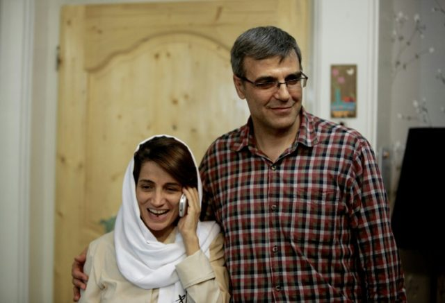 Iranian lawyer Nasrin Sotoudeh (L) speaks on the phone next to her husband Reza Khandan as they pose for a photo in their Tehran home in September 2013