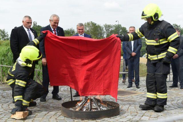 Czech President Milos Zeman (red tie)looks on as firefighters burn the oversized underwear