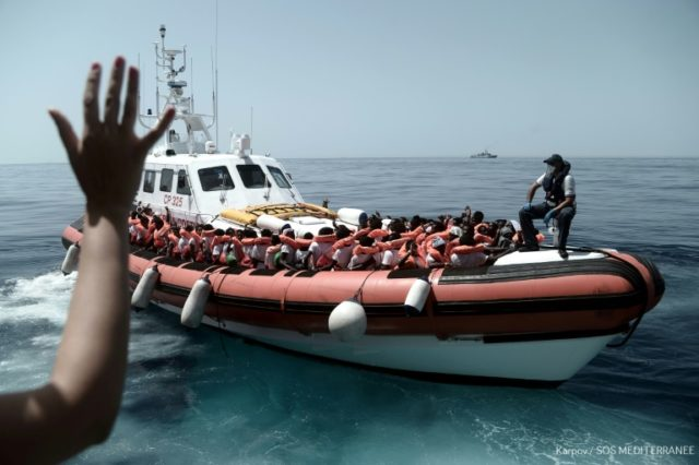 This handout picture from Medecins Sans Frontieres shows rescued migrants onboard an Italian coastguard ship following their transfer from the French NGO's ship Aquarius