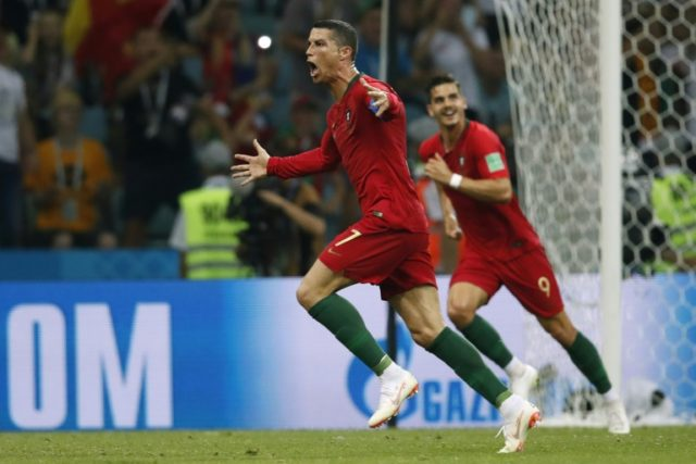 Cristiano Ronaldo celebrates the goal that completed his hat-trick and earned Portugal a draw against Spain
