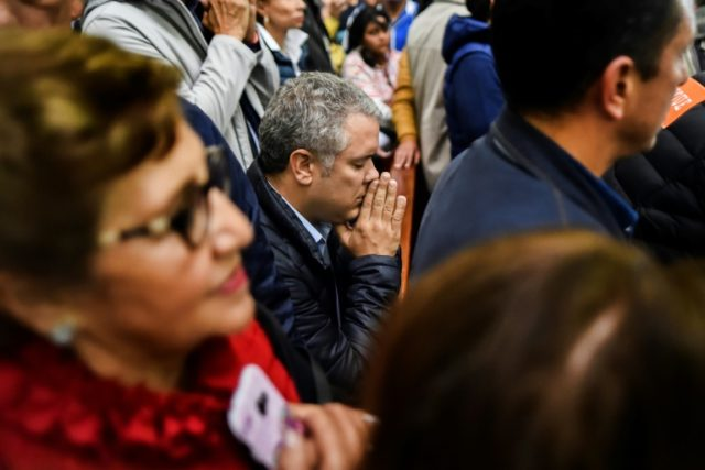 Ivan Duque (C), the frontrunner to be Colombia's next president, shown praying among supporters at a church, wants to rewrite a 2016 peace agreement with the FARC rebels