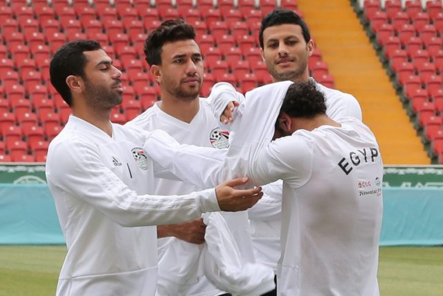 Three teammates helped Mohamed Salah get his traning top over his shoulder