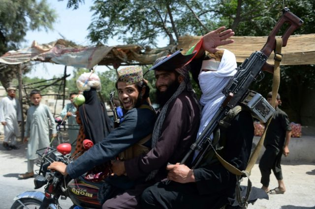 Afghan Taliban militants ride a motorbike as they took to the street to celebrate ceasefire on the second day of Eid