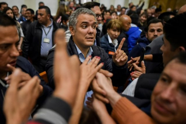 The front-runner in Colombia's presidential run-off, conservative senator Ivan Duque (C), wants to overhaul a 2016 peace deal with leftist FARC rebels