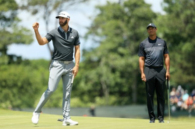 Dustin Johnson celebrates making a birdie on the seventh hole as Tiger Woods looks on during the second round of the US Open