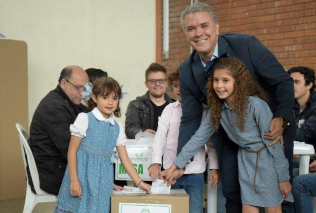 Conservative senator Ivan Duque casts his ballot surrounded by his children