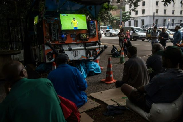 "Brazilian football team fans gather around a TV set attached to a cart in Sao Paulo on March 27, 2018; football is sacred in Latin America's biggest country and for many nothing will get in the way of watching the ""Selecao's"" games"