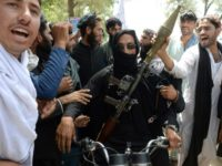 In jubilant scenes, an Afghan Taliban militant armed with a rocket launcher celebrated the ceasefire with residents of Jalalabad