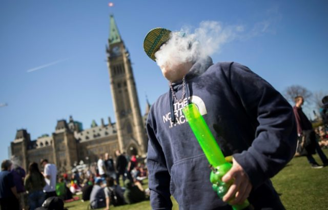 A man smokes marijuana to celebrate National Marijuana Day on Parliament Hill in Ottawa, Canada on April 20, 2016