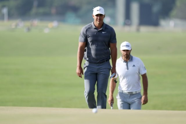 Brooks Koepka, foreground, walk off on the 18th green at Shinnecock Hills ahead of his friend Dustin Johnson, whose lead evaporated