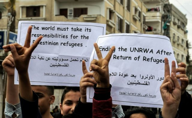 Palestinian school students shout slogans and hold placards in a protest against the US move to freeze funding for the UN agency for Palestinian refugees at the Rafah refugee camp in the southern Gaza Strip on March 28, 2018