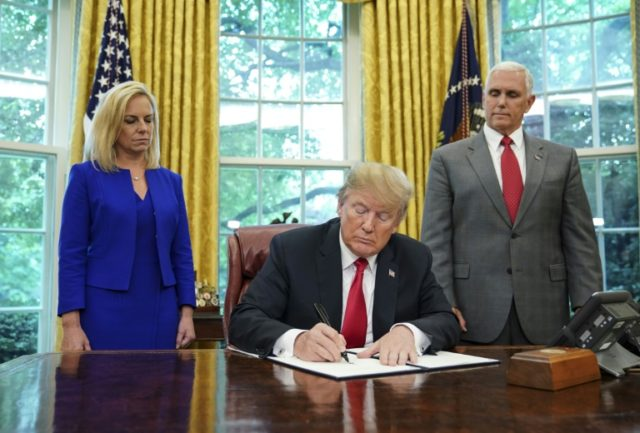 US President Donald Trump -- flanked by Homeland Security Secretary Kirstjen Nielsen (L) and Vice President Mike Pence -- signs an executive order to end family separations at the border