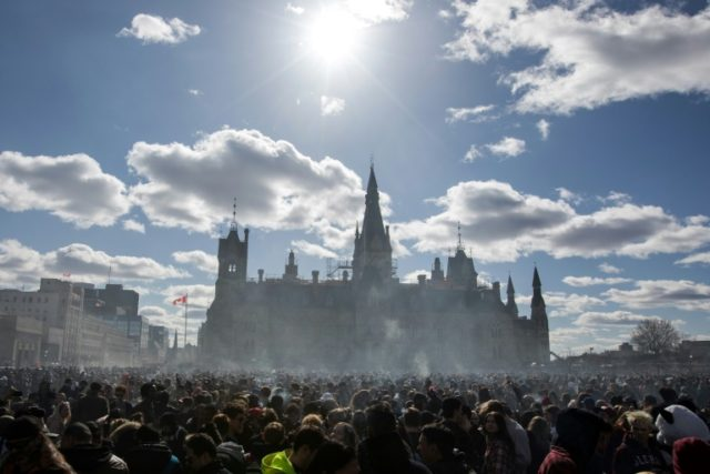 Smoke lingers over Parliament Hill as people consume marijuana on Parliament Hill in Ottawa, on April 20, 2018
