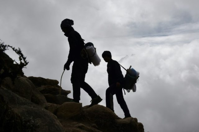Nepalese porters walk up a path high above the north-eastern town of Namche Bazar, as they head to pick up goods from a town at a higher elevation