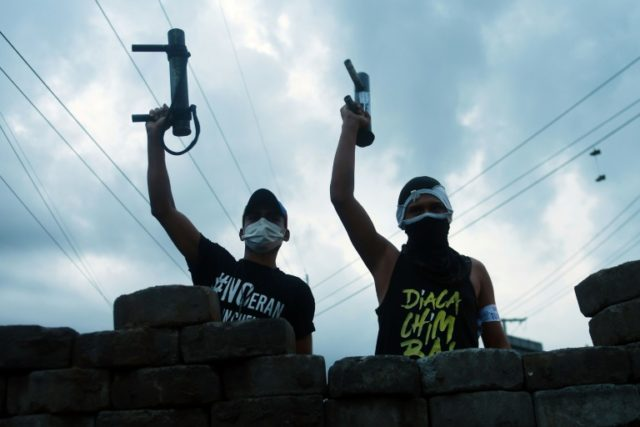 Anti-government protesters raise home-made mortarts, as they stand guard behind a barricade in Managua on June 20, 2018