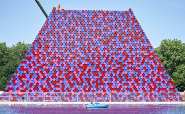 Workers build 'The Mastaba', made up of over 7,000 stacked coloured barrels by Bulgarian artist Christo Vladimirov Javachef on the lake in the Serpentine in Hyde Park in central London