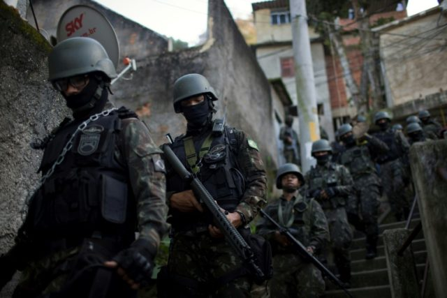 Members of Brazil's Armed Forces patrol inside the favelas of Rio de Janeiro, where they have been in charge of security since earlier this year