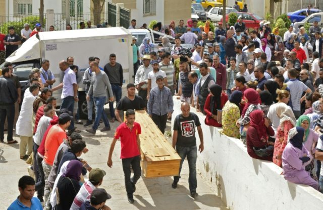 People wait to receive the bodies of loved ones in the Tunisian town of Sfax on June 4, 2018 after more than 50 migrants drowned in the Mediterranean