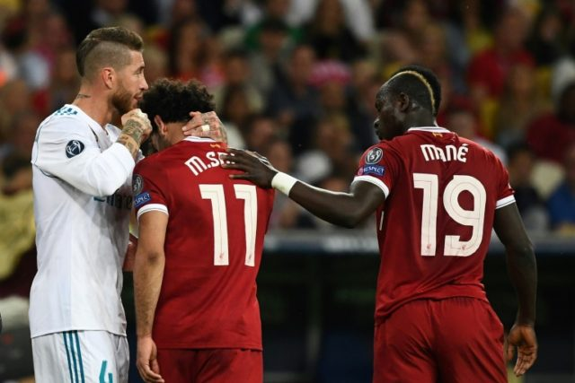 Sadio Mane (right) consoles Liverpool teammate Mohamed Salah as he leaves the pitch injured during the Champions League final
