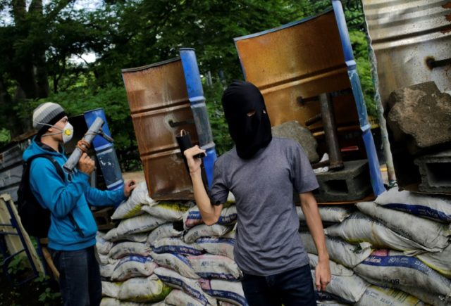 """Nicaraguan students with homemade mortars stand guard behind makeshift shields and barricades at Managua's National University (UNAN), days before reporting they were under """"attack"""" from police and paramilitaries"""