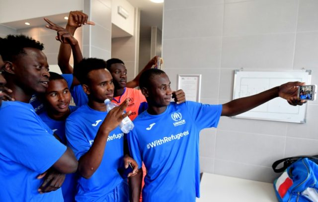 Young refugees capture the moment before taking on a team of former professional football players in Rome