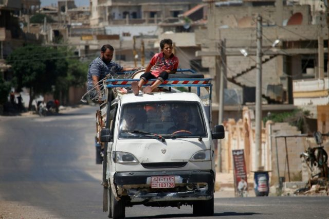 Civilians leave Daraa in southwestern Syria on June 23, 2018, after several days of intensified bombardment by Syrian regime forces