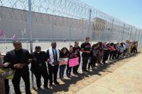 Protestors link arms after tying children's shoes and keys on the fence outside the Otay Mesa Detention Center during a demonstration against US immigration policy that separates children from their parents