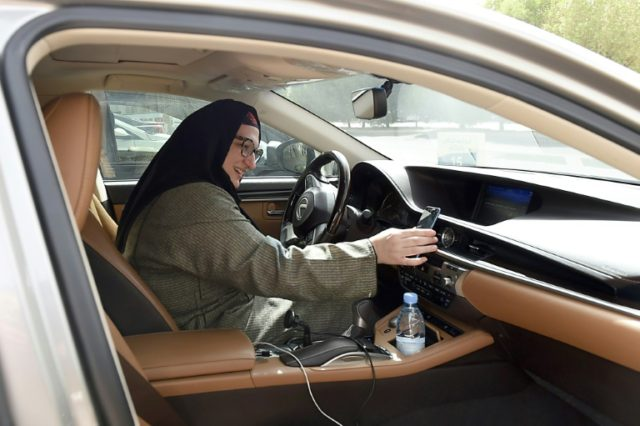 Saudi national and newly licensed Reem Farahat, a member of popular ride-hailing app Careem's new all-women chauffeur crew in Saudi Arabia, prepares to pick up a customer in the capital Riyadh on June 24, 2018