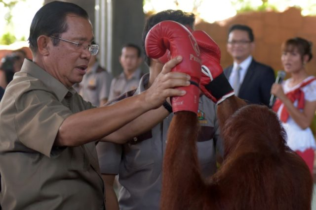 Cambodian Prime Minister Hun Sen holds an orangutan at a new zoo in Phnom Penh