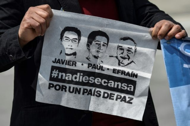 A man holds a handkerchief with the faces of three missing journalists from Ecuador who were found dead after being abducted
